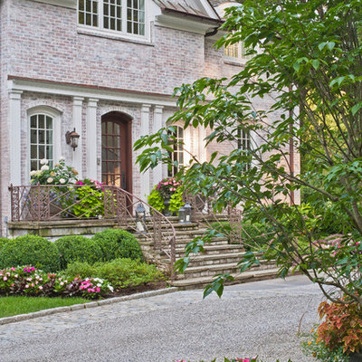 This is an example of a huge traditional partial sun front yard stone landscaping in New York.
