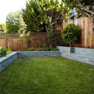 Foto di un piccolo orto in giardino minimal esposto a mezz'ombra dietro casa in estate con pavimentazioni in pietra naturale e recinzione in legno