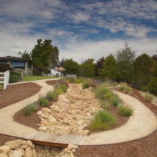 На фото: с высоким бюджетом большие солнечные, весенние участки и сады на заднем дворе в стиле рустика с освещенностью и покрытием из гравия