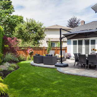 Photo of a huge traditional partial sun backyard stone formal garden in Vancouver with a fire pit for summer.