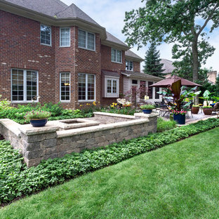 Photo of a large traditional partial sun backyard brick retaining wall landscape in Chicago for summer.