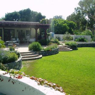 Mediterraner Garten hinter dem Haus mit Kamin, direkter Sonneneinstrahlung und Natursteinplatten in San Diego