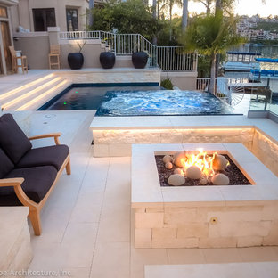 Design ideas for a mid-sized contemporary backyard stone landscaping in Orange County with a fire pit.