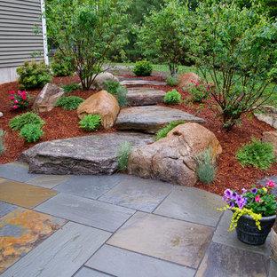 Idée de décoration pour un jardin arrière chalet de taille moyenne avec des pavés en pierre naturelle.