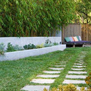 Exempel på en modern trädgård i slänt, med en stödmur