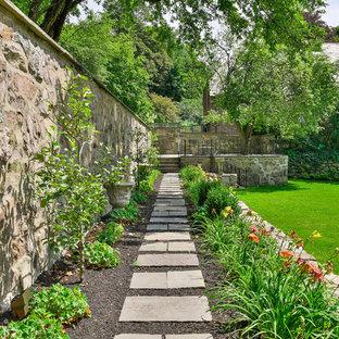 Inredning av en klassisk mellanstor bakgård i delvis sol, med en trädgårdsgång och naturstensplattor