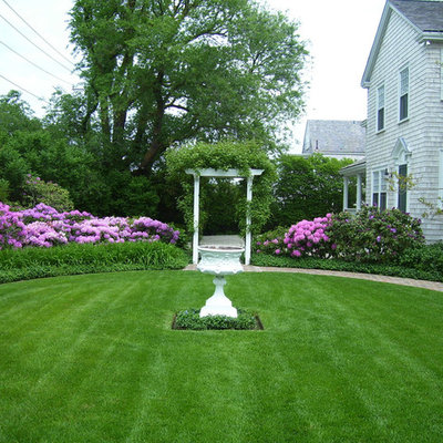 Inspiration for a large traditional full sun front yard brick water fountain landscape in Boston.