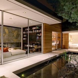 Mittelgroßer Mid-Century Garten neben dem Haus mit Teich, direkter Sonneneinstrahlung und Betonplatten in Los Angeles