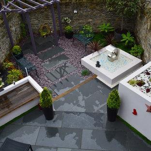 Diseño de jardín actual, pequeño, en patio trasero, con jardín de macetas y adoquines de piedra natural