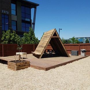 Idéer för att renovera en stor rustik bakgård i full sol som tål torka, med en lekställning och trädäck
