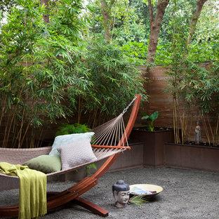 Exemple d'un jardin à la française asiatique de taille moyenne avec du gravier et un mur de soutènement.