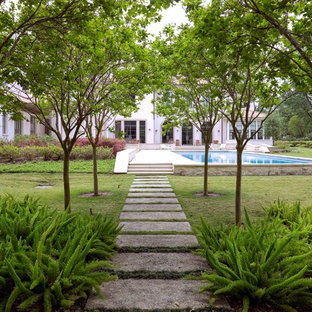 This is an example of a huge mediterranean shade backyard concrete paver formal garden in Houston for summer.