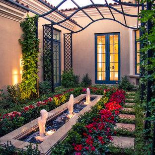 Ejemplo de jardín mediterráneo, pequeño, en patio, con fuente