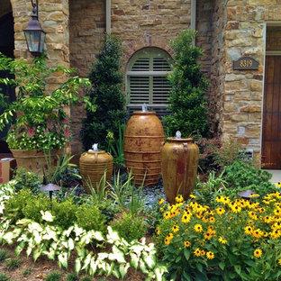 Imagen de jardín francés y parterre de flores, mediterráneo, grande, en verano, en patio delantero, con exposición total al sol y gravilla