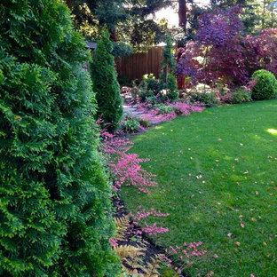 Aménagement d'un grand jardin à la française arrière classique au printemps avec une exposition ombragée et un paillis.