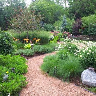 Aménagement d'un jardin arrière classique l'automne avec un gravier de granite et une entrée ou une allée de jardin.