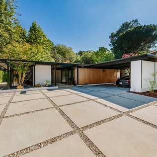 Photo of a large midcentury front yard full sun driveway in Los Angeles with concrete pavers.