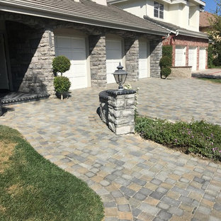 Photo of a mid-sized victorian front yard concrete paver driveway in Orange County.