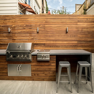 Photo of a small modern partial sun backyard concrete paver retaining wall landscape in Chicago for summer.