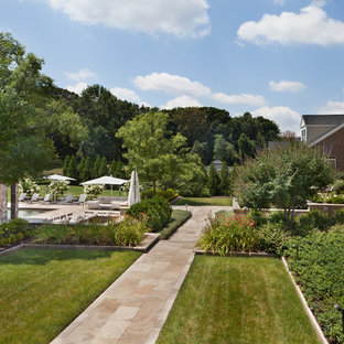 Photo of a large traditional full sun backyard stone landscaping in DC Metro.