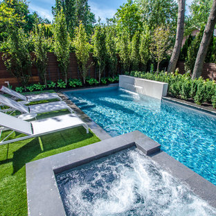 Photo of a small contemporary full sun backyard stone water fountain landscape in Toronto for summer.