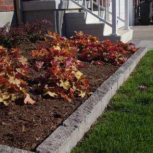 This is an example of a small modern full sun front yard mulch formal garden in Toronto for spring.