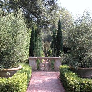 Photo of a large mediterranean backyard brick landscaping in Santa Barbara.