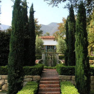 This is an example of a large mediterranean backyard brick landscaping in Santa Barbara.