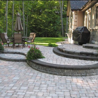 Inspiration for a mid-sized traditional full sun backyard stone landscaping in Toronto.