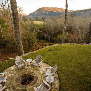 Design ideas for a mid-sized rustic full sun backyard stone landscaping in Other with a fire pit.