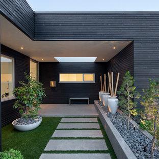 Photo of a modern partial sun front yard concrete paver garden path in Portland.