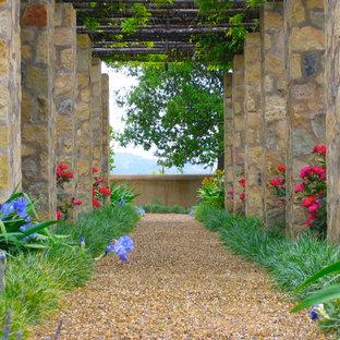 Design ideas for a mediterranean retaining wall landscape in Orange County.