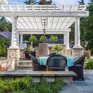 Photo of a mid-sized contemporary full sun backyard stone landscaping in Chicago with a fire pit for summer.