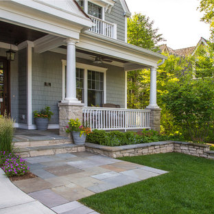 This is an example of a mid-sized contemporary full sun front yard stone retaining wall landscape in Chicago for summer.