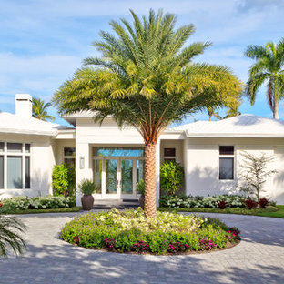 Inspiration for a tropical full sun front yard brick driveway in Miami.