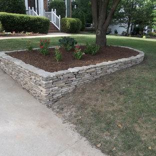 Свежая идея для дизайна: участок и сад среднего размера на переднем дворе в стиле ретро с подъездной дорогой и подпорной стенкой - отличное фото интерьера
