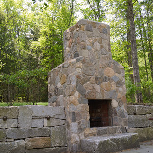 Inspiration for a rustic backyard stone landscaping in Boston with a fireplace.