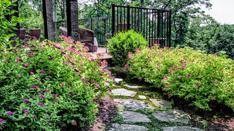 Natural stone path flanked by Spirea and Boxwood