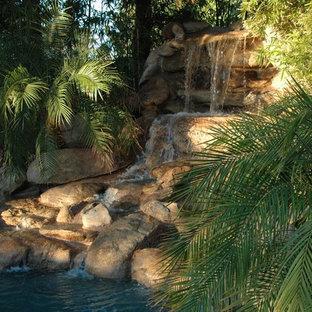 Idee per un grande giardino formale tropicale esposto a mezz'ombra davanti casa con fontane e pavimentazioni in pietra naturale