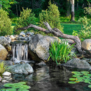 Design ideas for a large rustic backyard water fountain landscape in New York for spring.