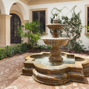This is an example of a mid-sized mediterranean partial sun courtyard stone landscaping in Miami.