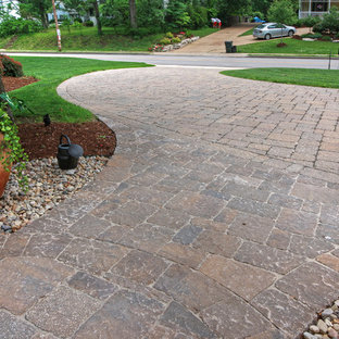 Photo of a large traditional partial sun front yard concrete paver driveway in St Louis for summer.