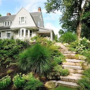 Aménagement d'un grand jardin à la française contemporain l'été avec une exposition ombragée, une pente, une colline ou un talus, des pavés en pierre naturelle et une entrée ou une allée de jardin.