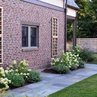 Idéer för stora vintage formella trädgårdar i delvis sol längs med huset, med en trädgårdsgång och naturstensplattor