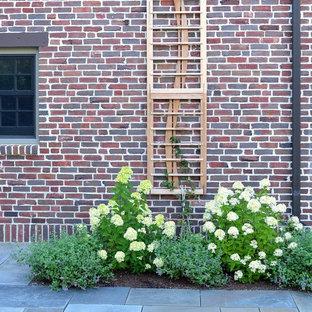 Réalisation d'un grand jardin à la française latéral tradition avec une entrée ou une allée de jardin, une exposition partiellement ombragée et des pavés en pierre naturelle.