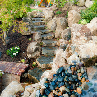 This is an example of a large mediterranean partial sun backyard stone water fountain landscape in Portland for spring.