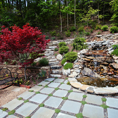 Photo of a mid-sized traditional full sun backyard stone landscaping in Charlotte for summer.