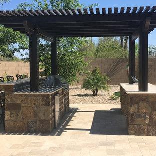 Exotisk inredning av en mellanstor bakgård i delvis sol som tål torka, med en öppen spis och naturstensplattor
