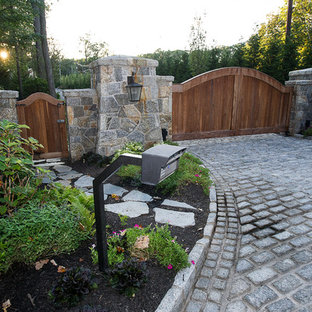 Country front yard driveway in New York with a garden path and concrete pavers.