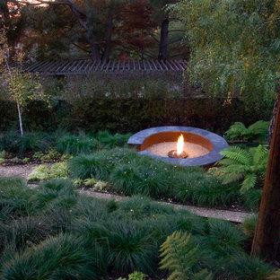 Exemple d'un jardin arrière industriel avec un foyer extérieur et un gravier de granite.